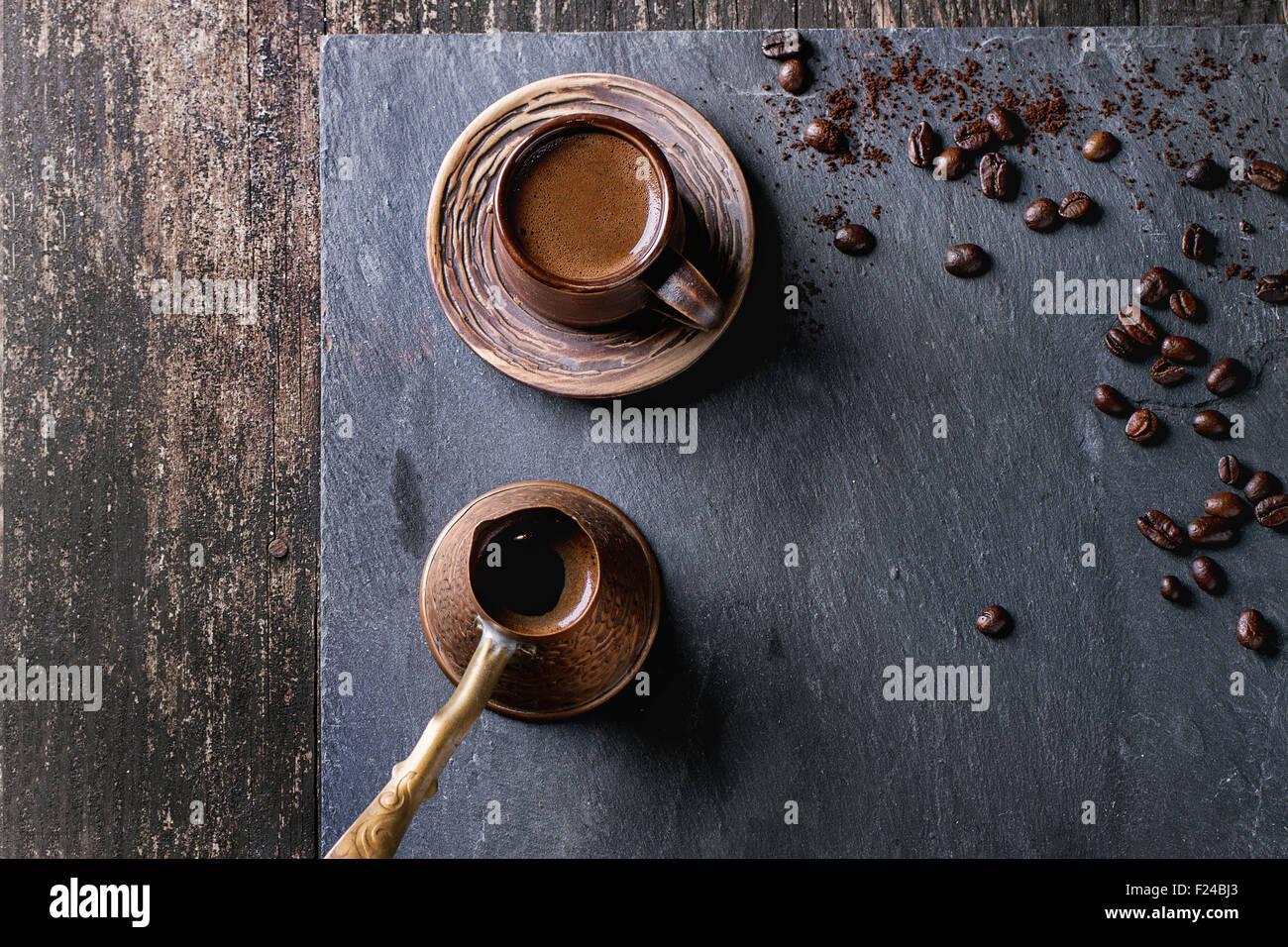 Ceramica marrone tazza di caffè, rame antico cezve e i chicchi di caffè. Oltre nero ardesia come sfondo. Immagini Stock