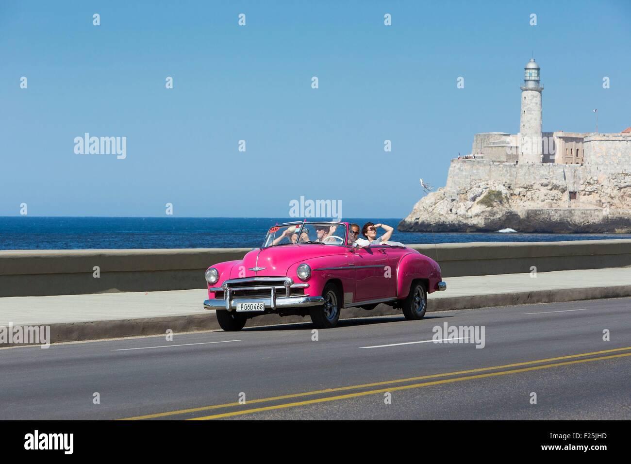 Cuba, Ciudad de la Habana Province, La Havana, vettura americana sul Malecon e il faro del Castillo de los Tres Immagini Stock