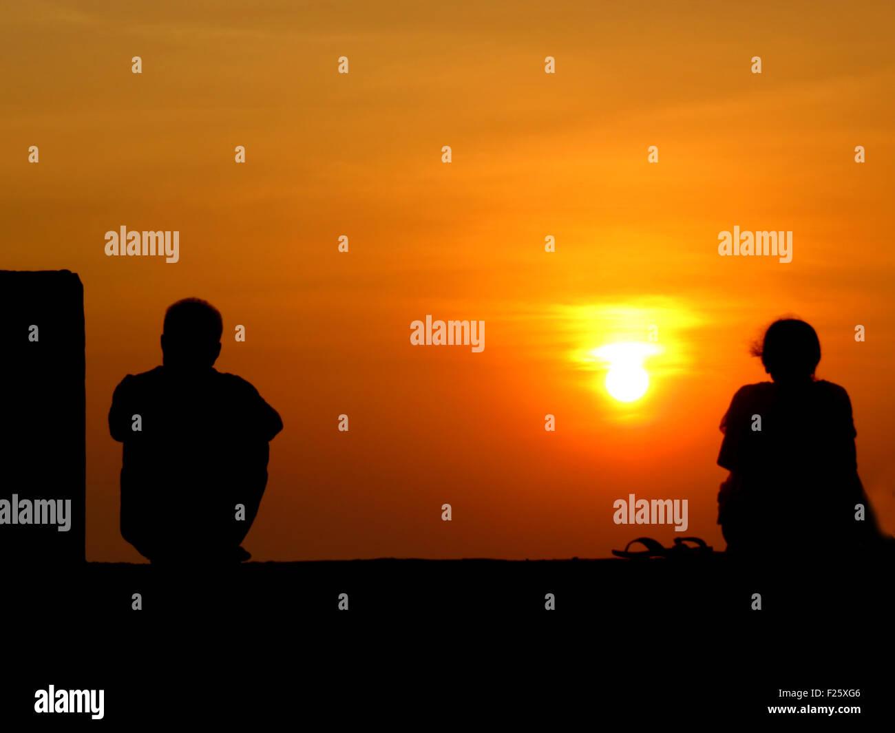 Una immagine metaforica delle sagome di un separato giovane sullo sfondo di un tramonto. Immagini Stock