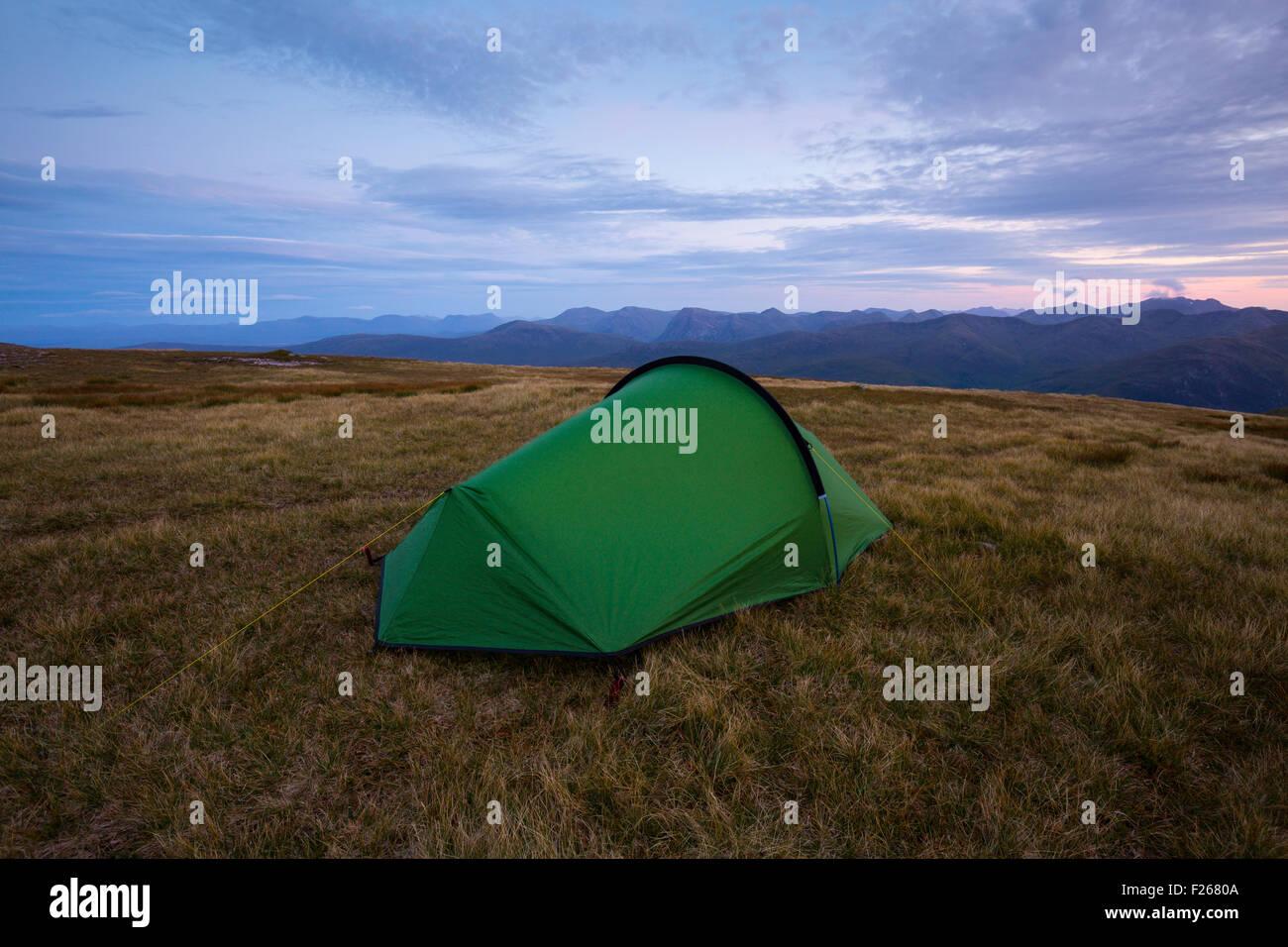 Una tenda si accamparono nel Mamores, Scozia, con i massicci montuosi di Glen Coe in background Immagini Stock