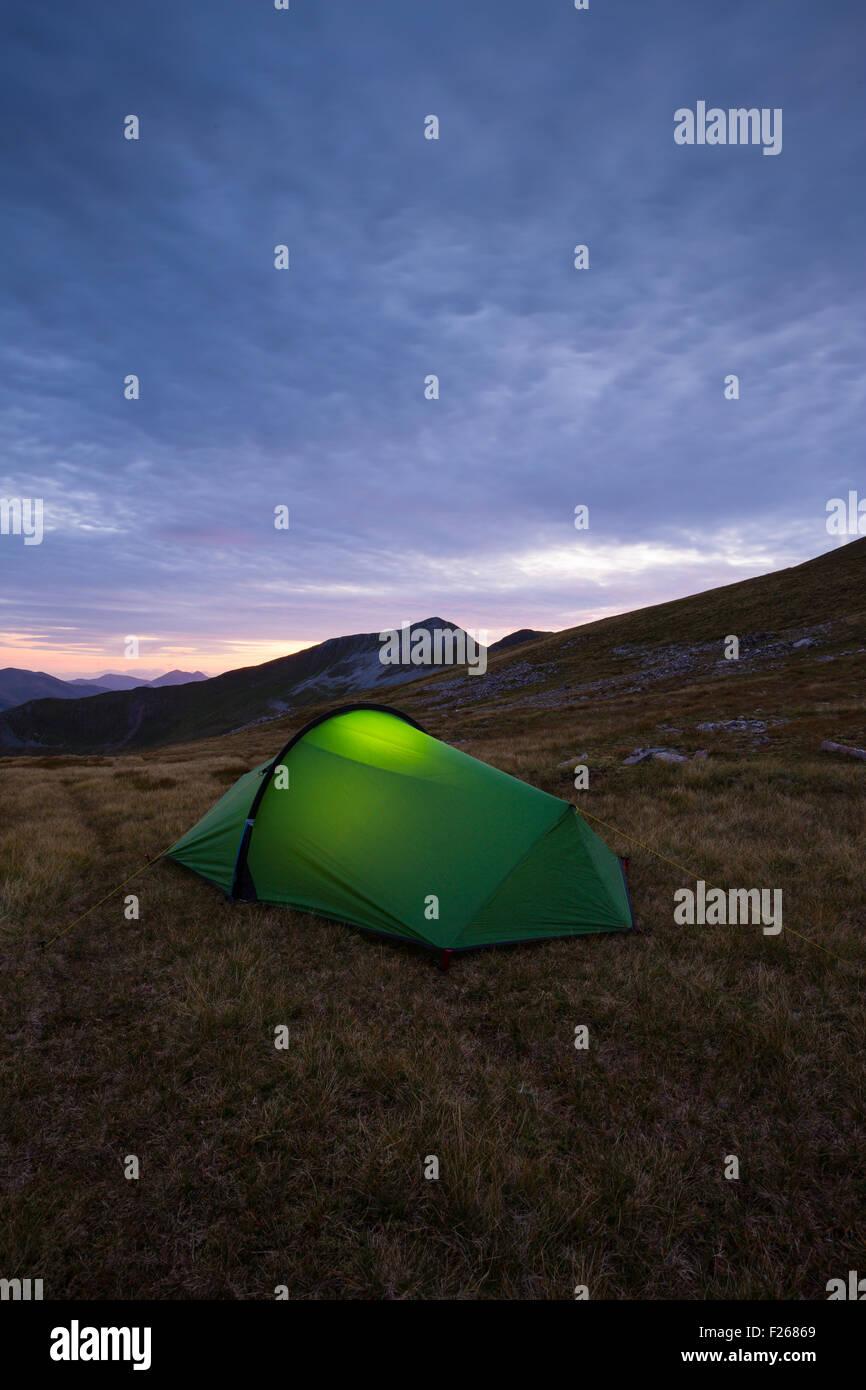 Fiaccola accesa tenda nell'alto Mamores mentre il campeggio selvaggio in Scozia Immagini Stock