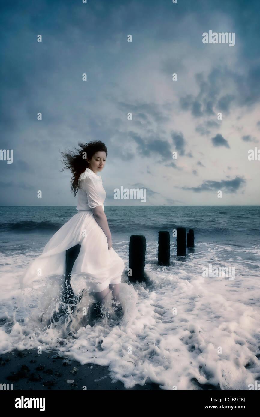 Una ragazza in un abito bianco è seduto su un palo di legno in mare Immagini Stock