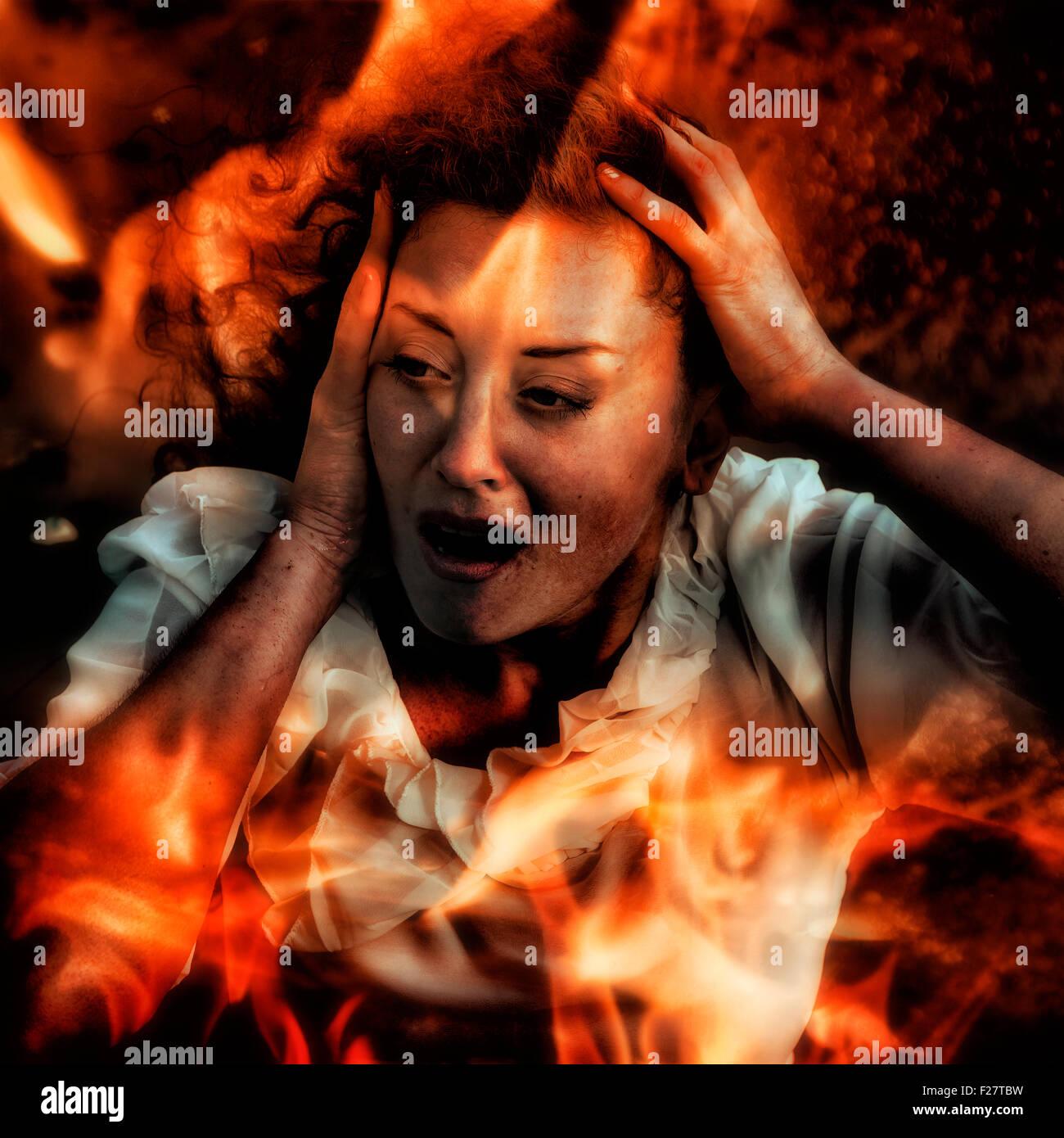 Una donna che guarda attraverso le fiamme, urlando Foto Stock
