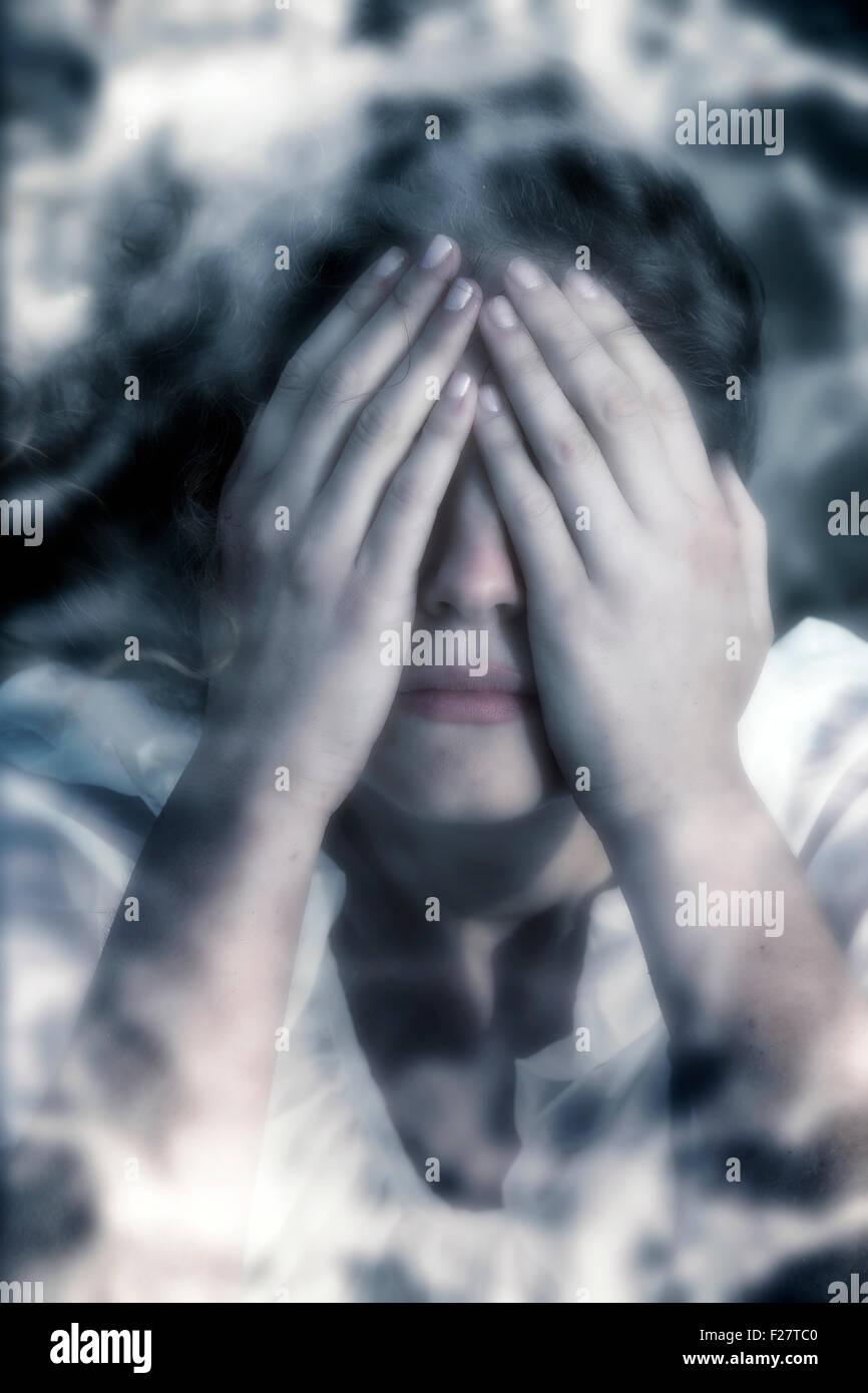 Una donna in difficoltà, nascondersi dietro le mani Immagini Stock