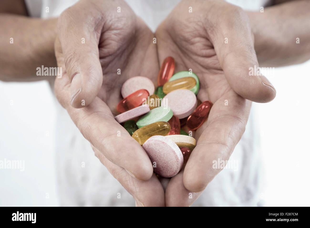 Medico maschio con le mani in mano che mostra le pillole di prescrizione, Baviera, Germania Immagini Stock