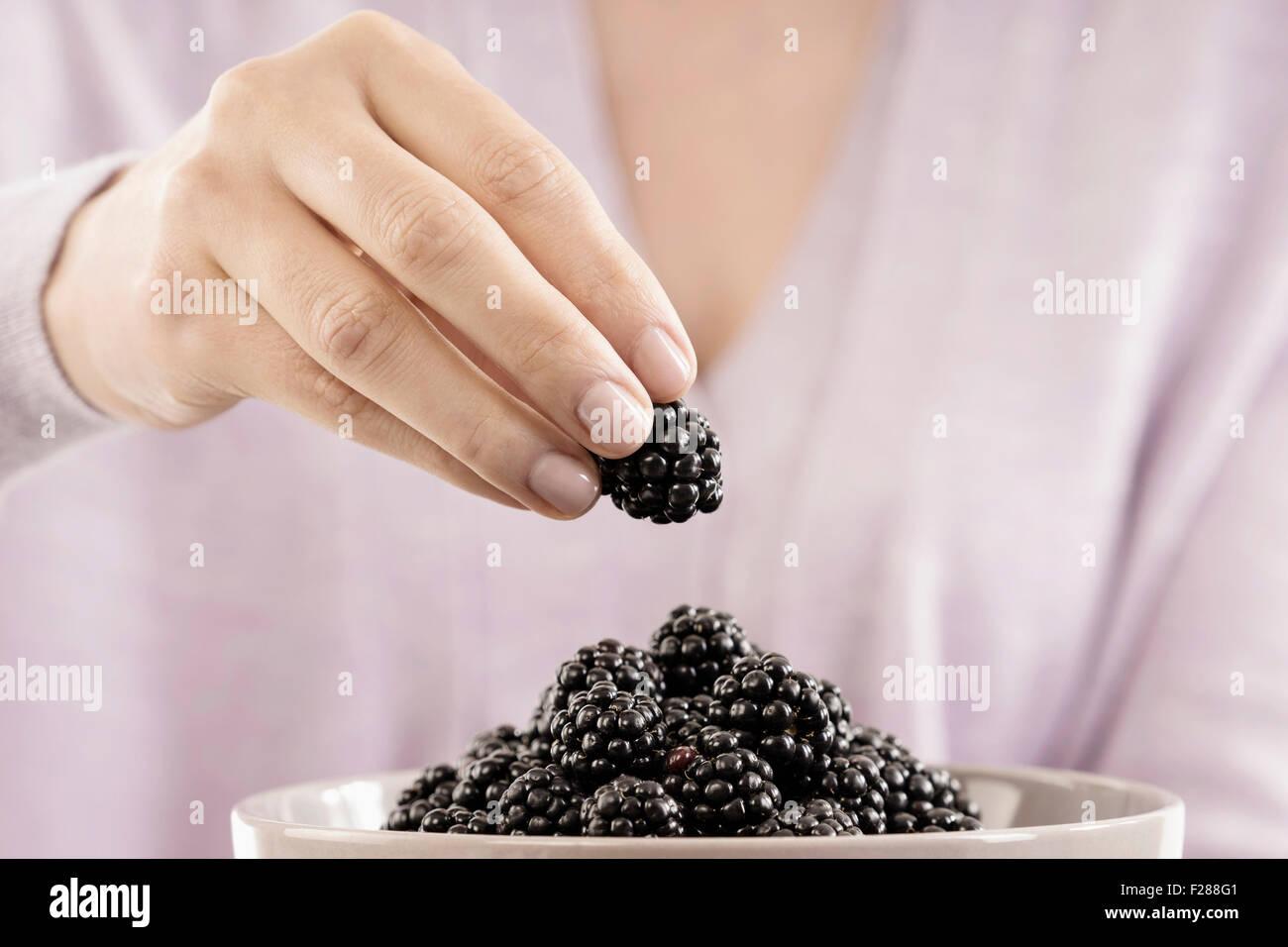 Metà vista in sezione della donna mangiare blackberry, Baviera, Germania Immagini Stock