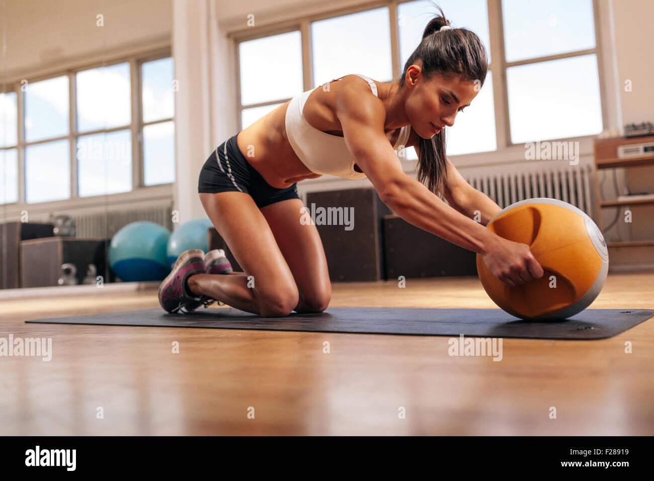 Forte giovane donna facendo un intenso allenamento con kettlebell in palestra. Giovane donna muscolare facendo esercizio Immagini Stock