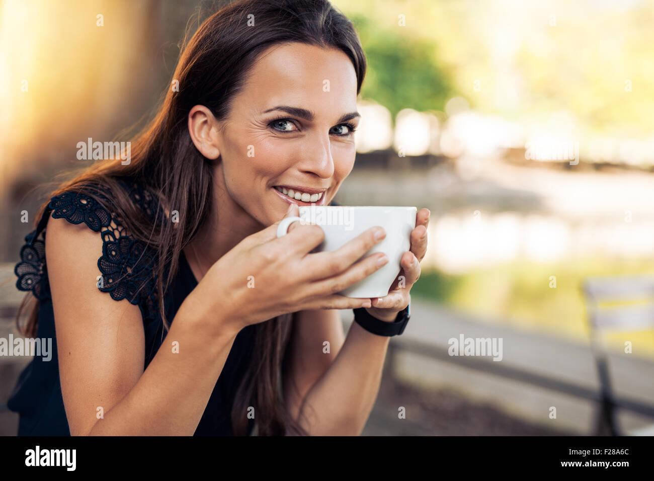Bella giovane donna in possesso di una tazza di caffè guardando la telecamera sorridendo. Femmina allegro gustando Immagini Stock