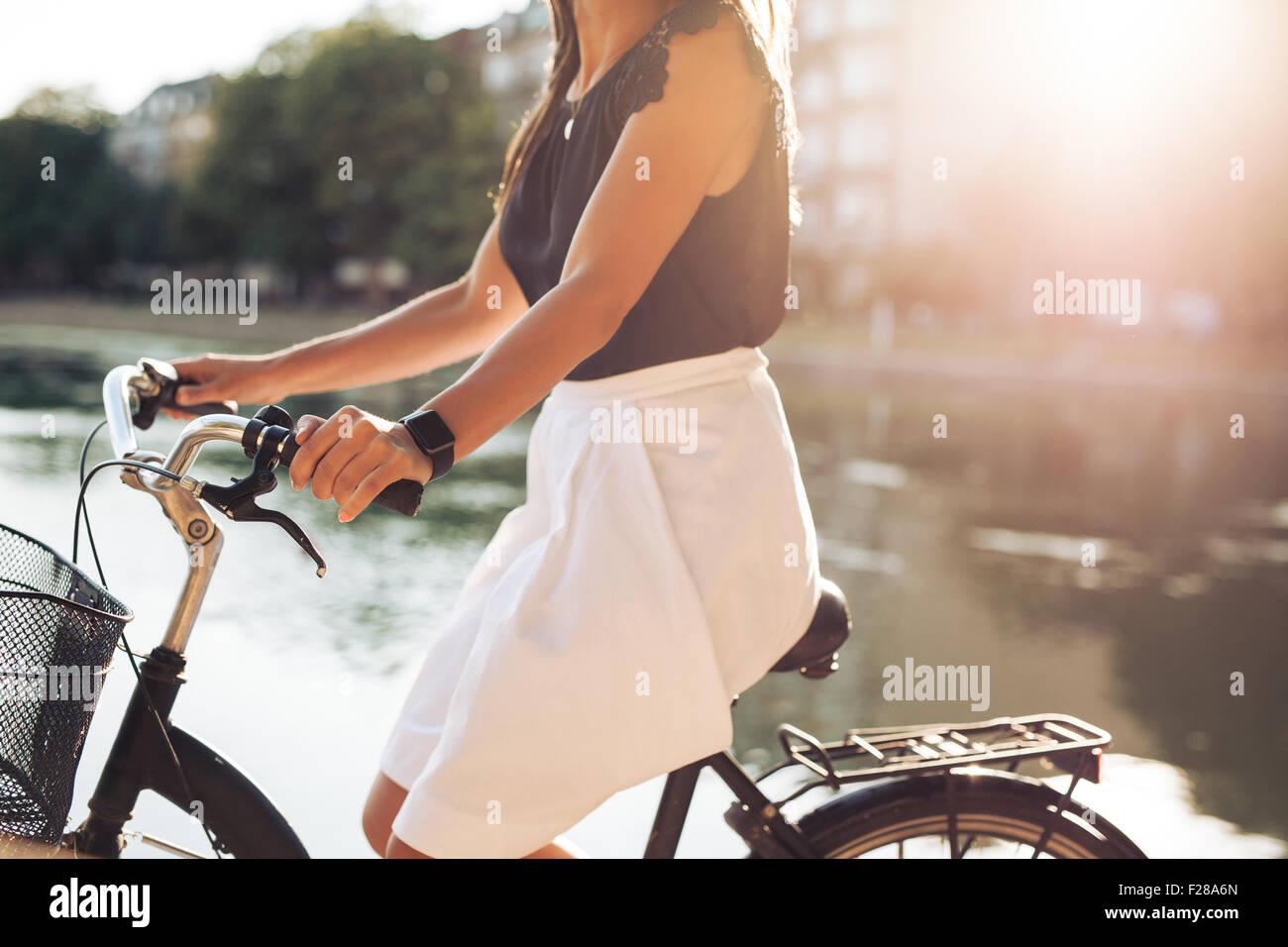 Immagine ritagliata giovane femmina la sua equitazione Bicicletta nei pressi di un laghetto. Donna in bicicletta Immagini Stock