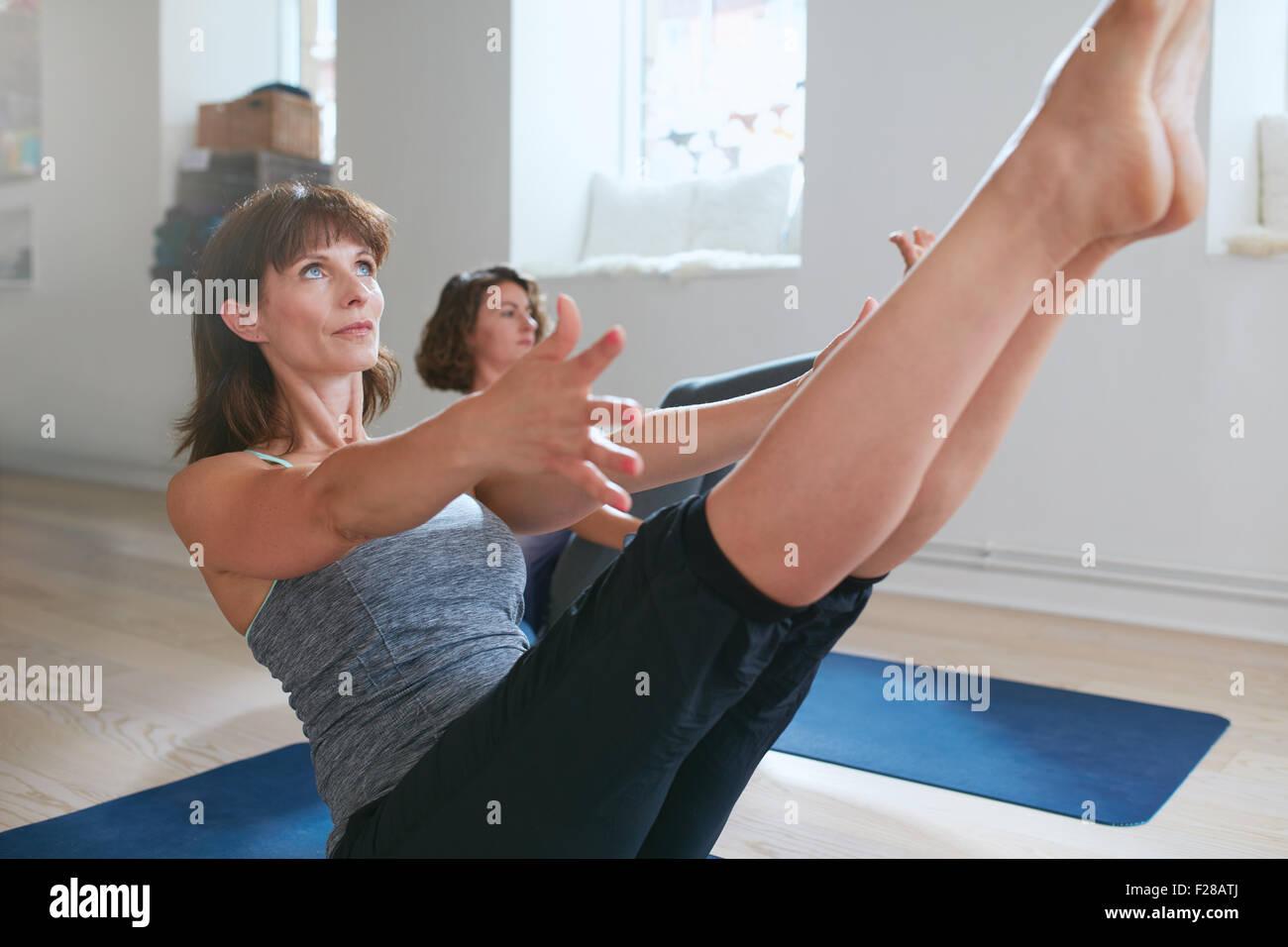 Le donne la pratica di stretching e yoga esercizio di allenamento insieme in un club benessere palestra di formazione Immagini Stock
