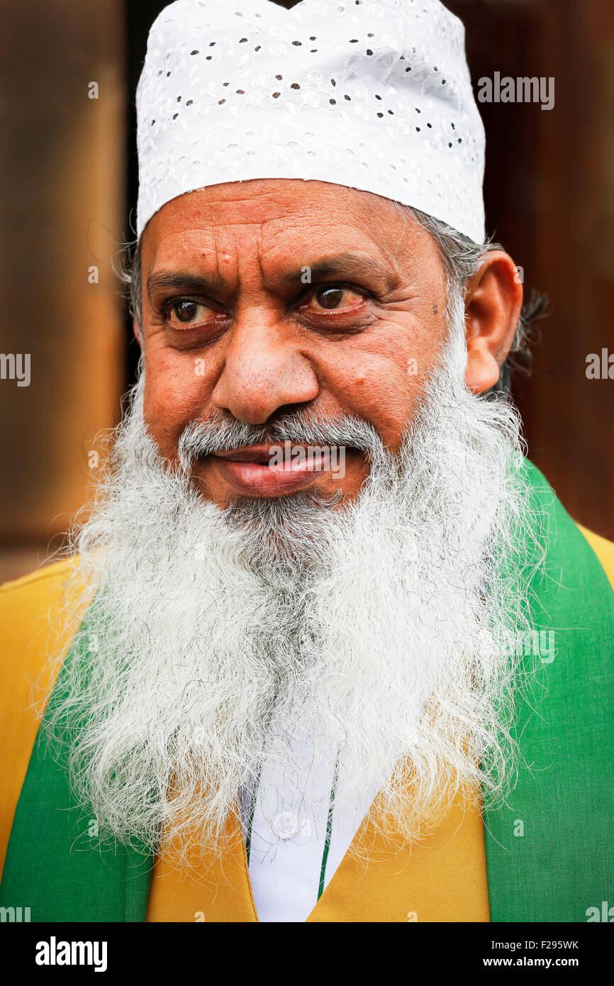 Anziani uomo pakistano indossa foulard religiosa e cotone hat, Glasgow, Scotland, Regno Unito Immagini Stock