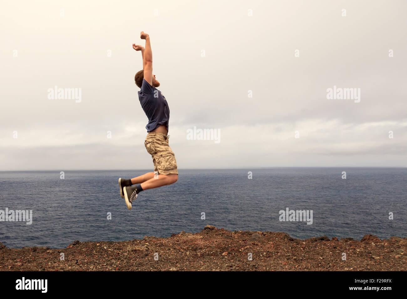 Il successo o il concetto di win - uomo gioioso jumping outdoor Immagini Stock