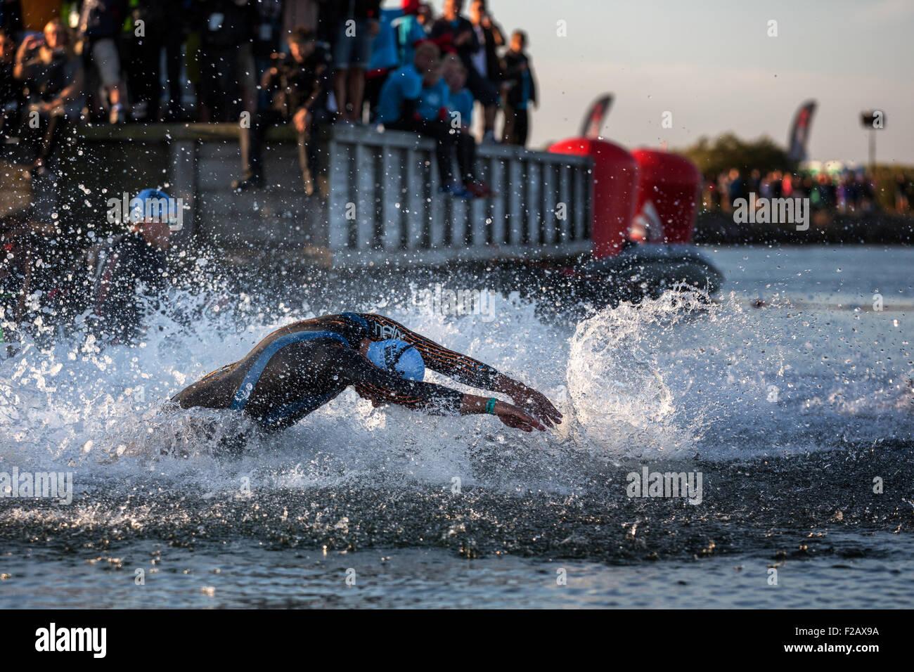 I partecipanti di Ironman Triathlon di partenza della gara nel surf, Amager Strandpark, Copenhagen, Danimarca Immagini Stock