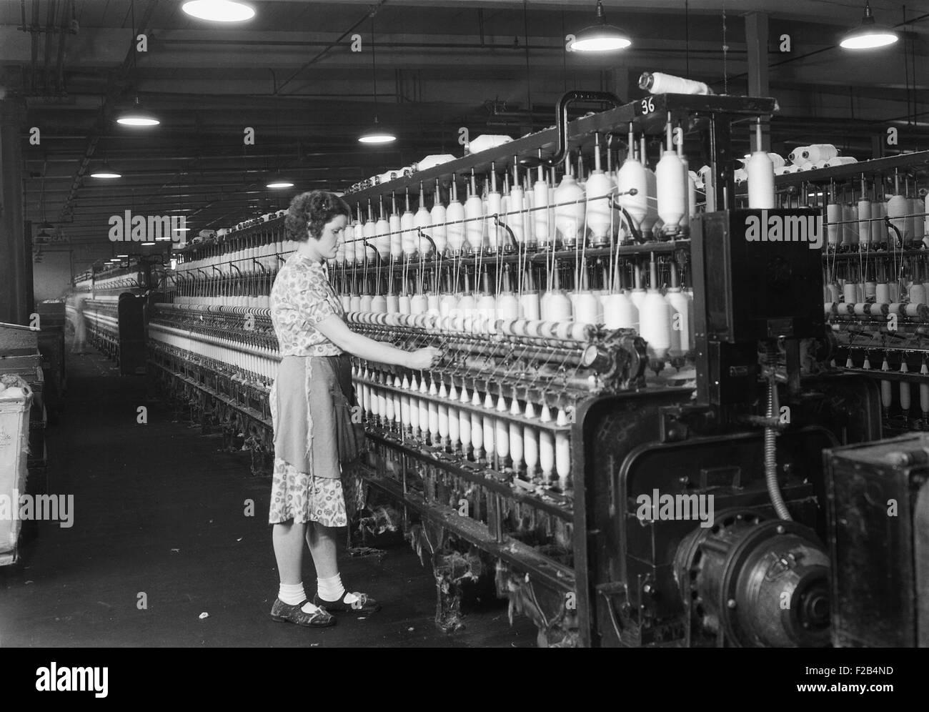 La donna in piedi alla lunga fila di bobine, ad una fabbrica tessile. Millville, N.J. 1936. Foto di Lewis Hine. Immagini Stock