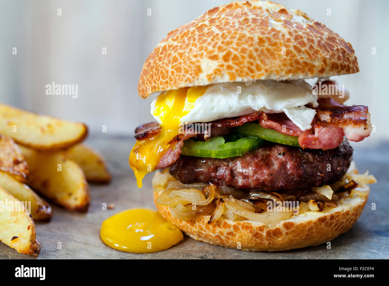 Hamburger di manzo con pancetta e uova in camicia Immagini Stock