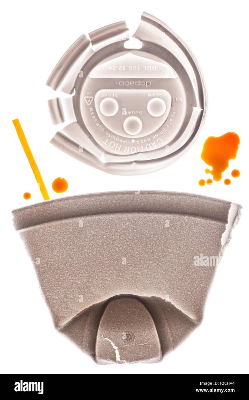 Styrofoam appiattita tazza da caffè con cappuccio sopra e giallo agitare stick sul tavolo luminoso con gocce Immagini Stock