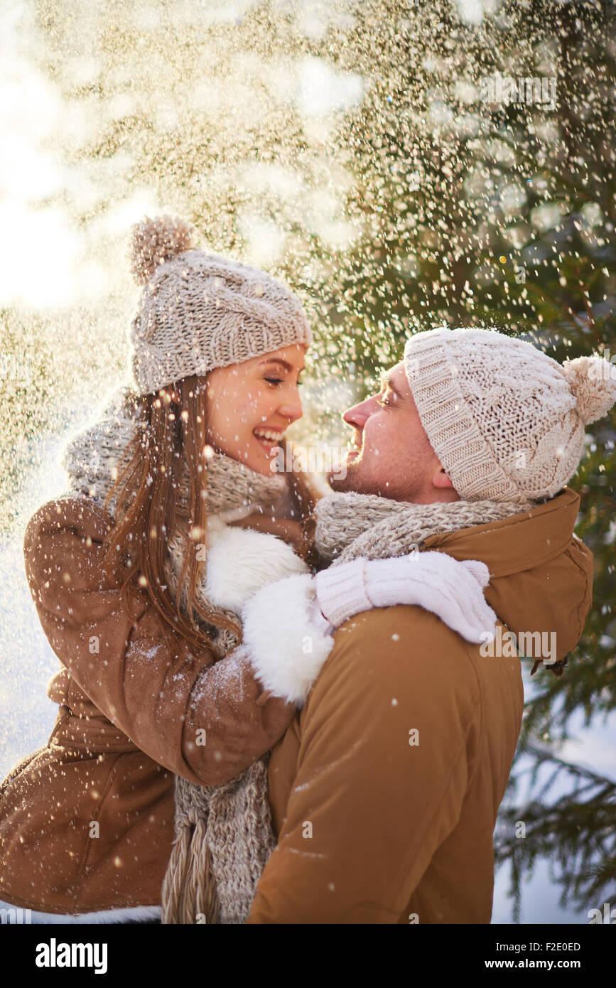 Amorosi l uomo e la donna godendo di nevicata Immagini Stock