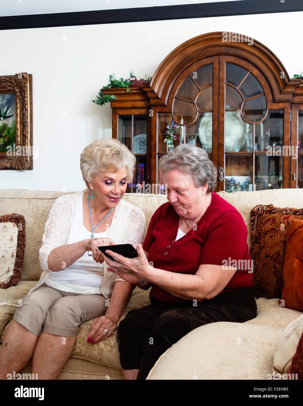 Due senior caucasica donne, sorelle, capire come utilizzare un Kindle fuoco. Stati Uniti d'America Foto Stock