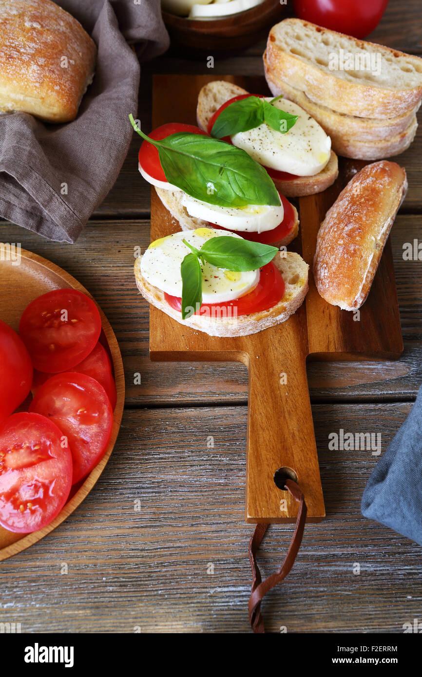 Pane con pomodoro e formaggio sulla scheda, cibo Immagini Stock