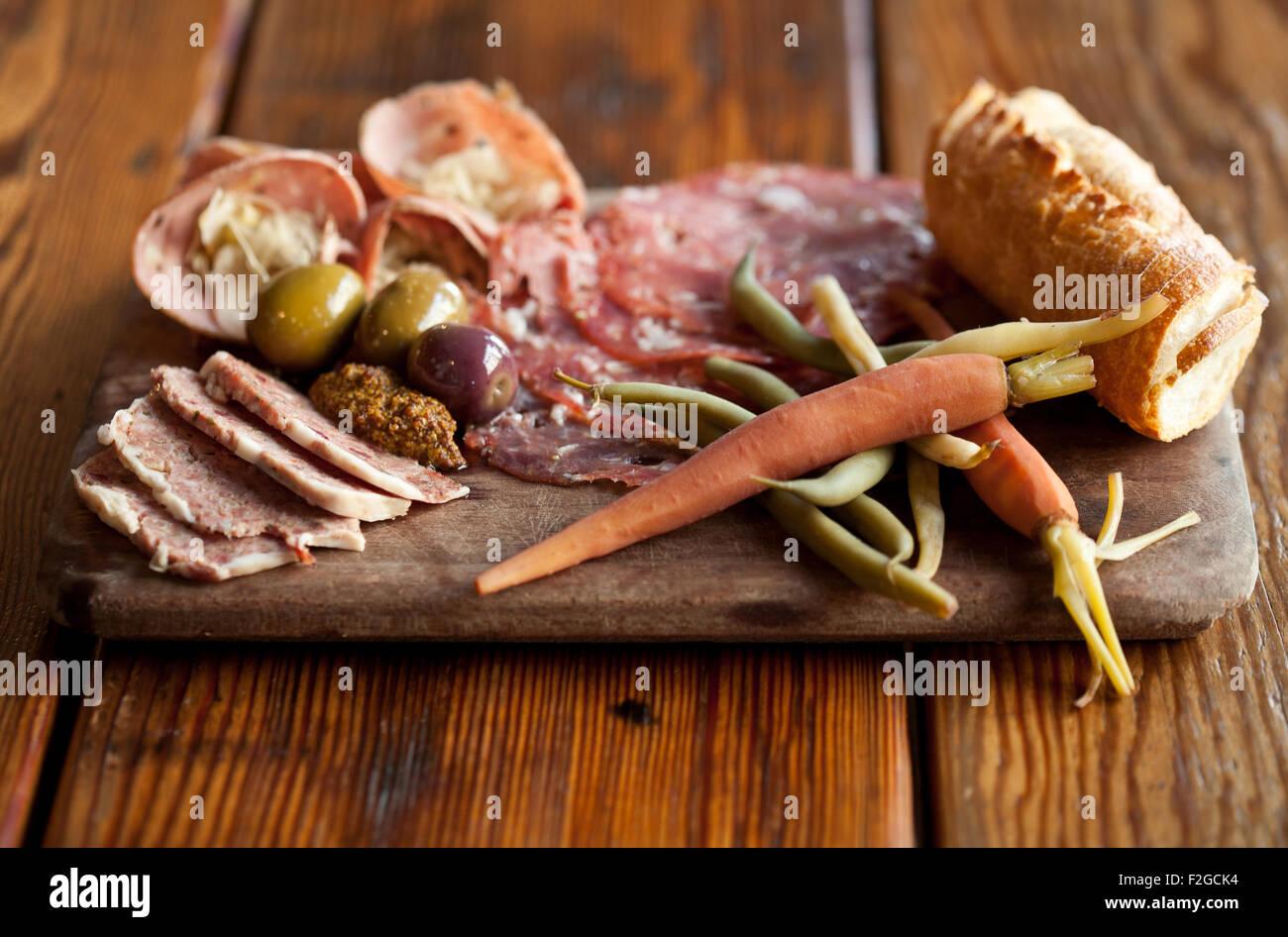 Salumi con il tedesco Bierwurst con saur kraut, Soppressata salami, Verdure sottaceto, olive, pane, senape Immagini Stock