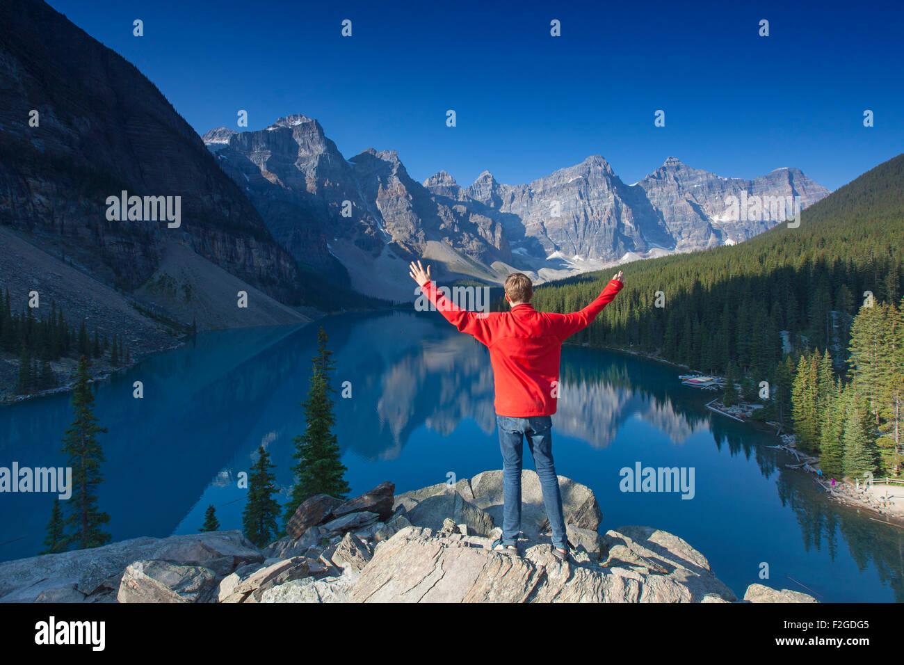 Turistico con le braccia aperte sul look-out point guardando sopra il Lago Moraine nella Valle dei Dieci Picchi, Immagini Stock