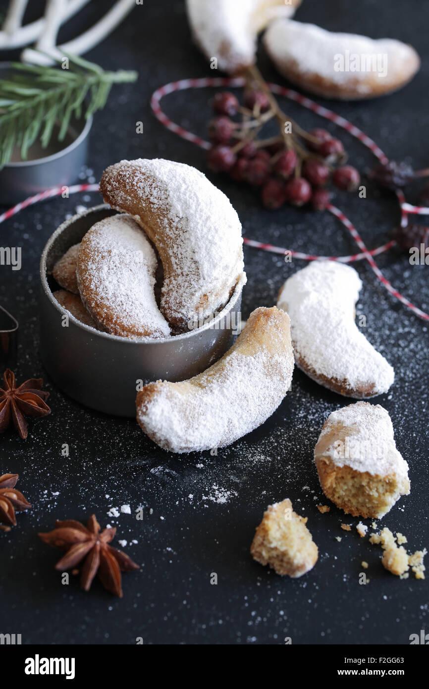Vanillekipferl (a forma di mezzaluna biscotti alla vaniglia) essendo guarnita con zucchero vanigliato Immagini Stock