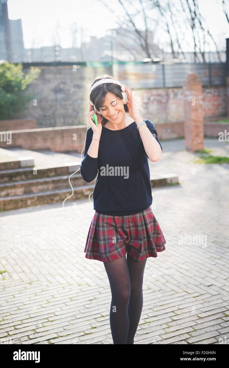Ginocchio la figura di un giovane piuttosto marrone capelli ragazza caucasica ascolto di musica con cuffie, tenendo Immagini Stock