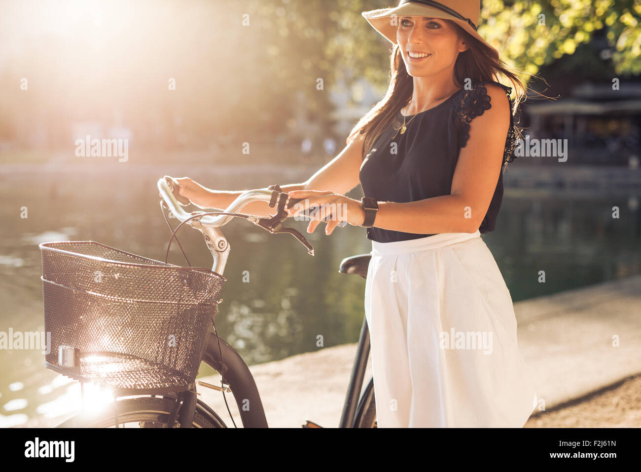 Colpo all'aperto di una bella donna giovane con una bicicletta nel parco durante l'estate. Femmina con un Immagini Stock