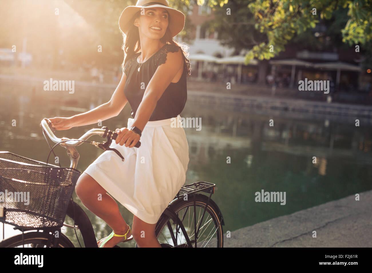 Ritratto di giovane e bella donna in bicicletta lungo una strada nei pressi di stagno su un giorno d'estate. Immagini Stock