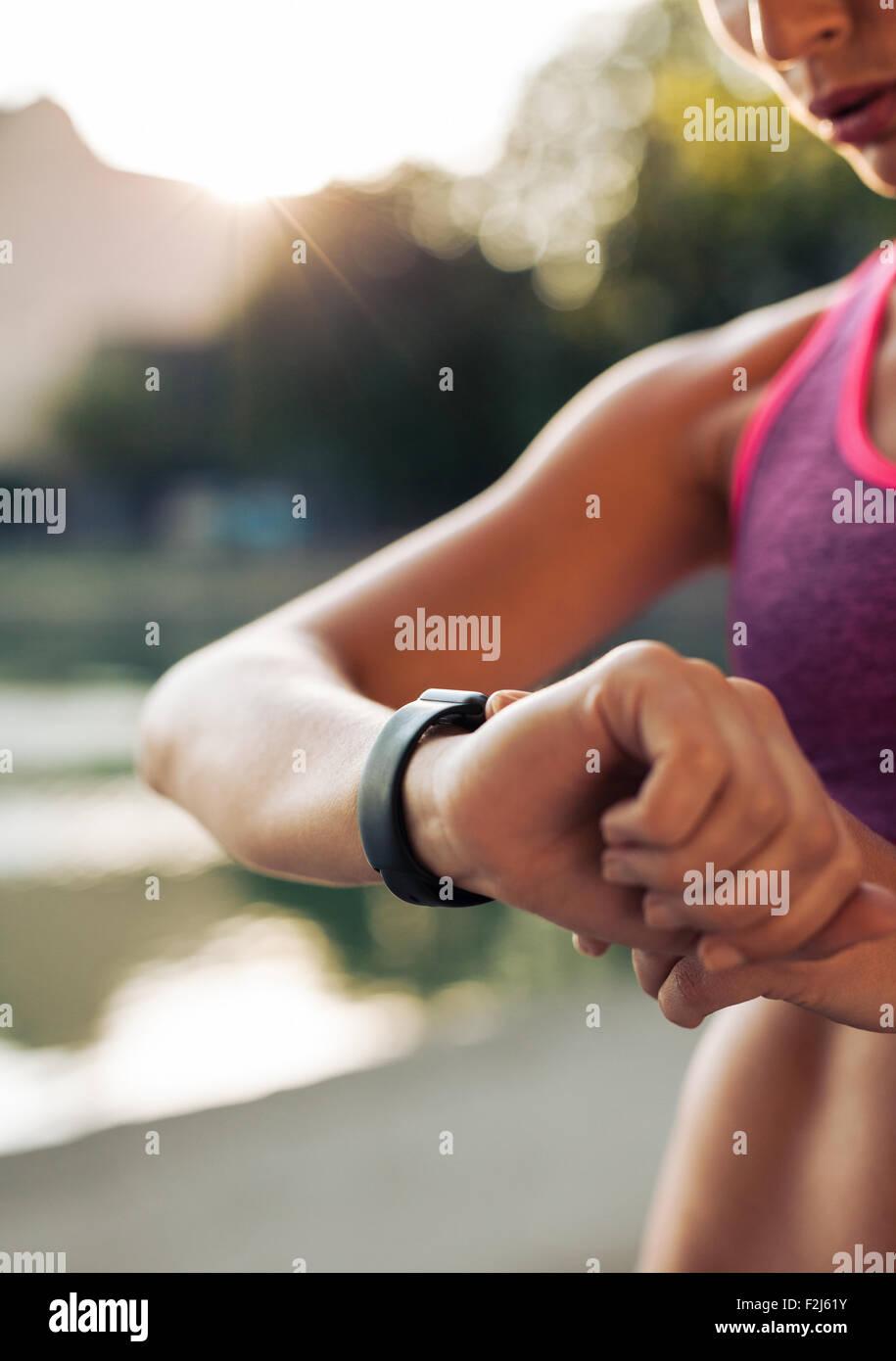 Immagine ravvicinata di giovane donna pareggiatore pronto per funzionare insieme e guardando sport smartwatch. Femmina Immagini Stock