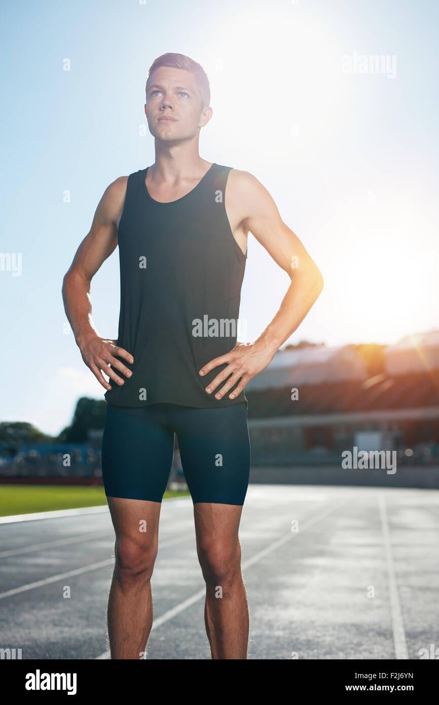 Montare il giovane uomo in piedi con le mani sui fianchi che guarda lontano. Determinato atleta maschio preparando Immagini Stock