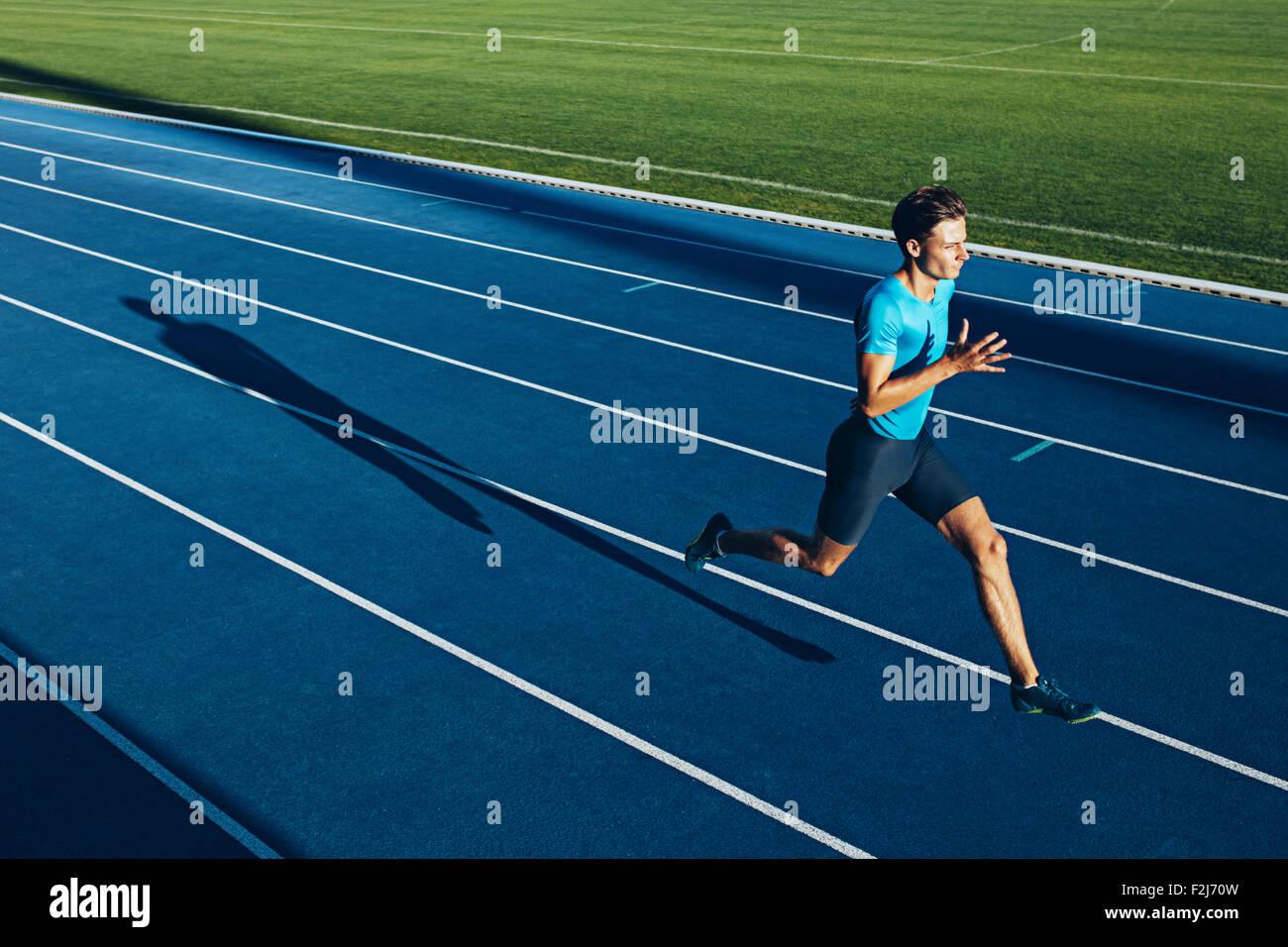 Inquadratura di un giovane atleta maschio training su una pista. Sprinter in esecuzione su piste per atletica. Immagini Stock