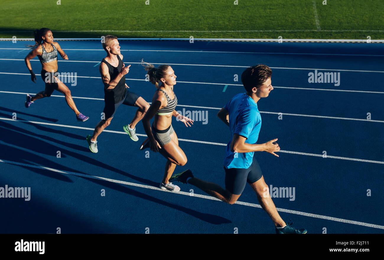 Gruppo di atleti e multirazziale la pratica della corsa su pista. Maschio e femmina gli atleti durante la sessione Immagini Stock