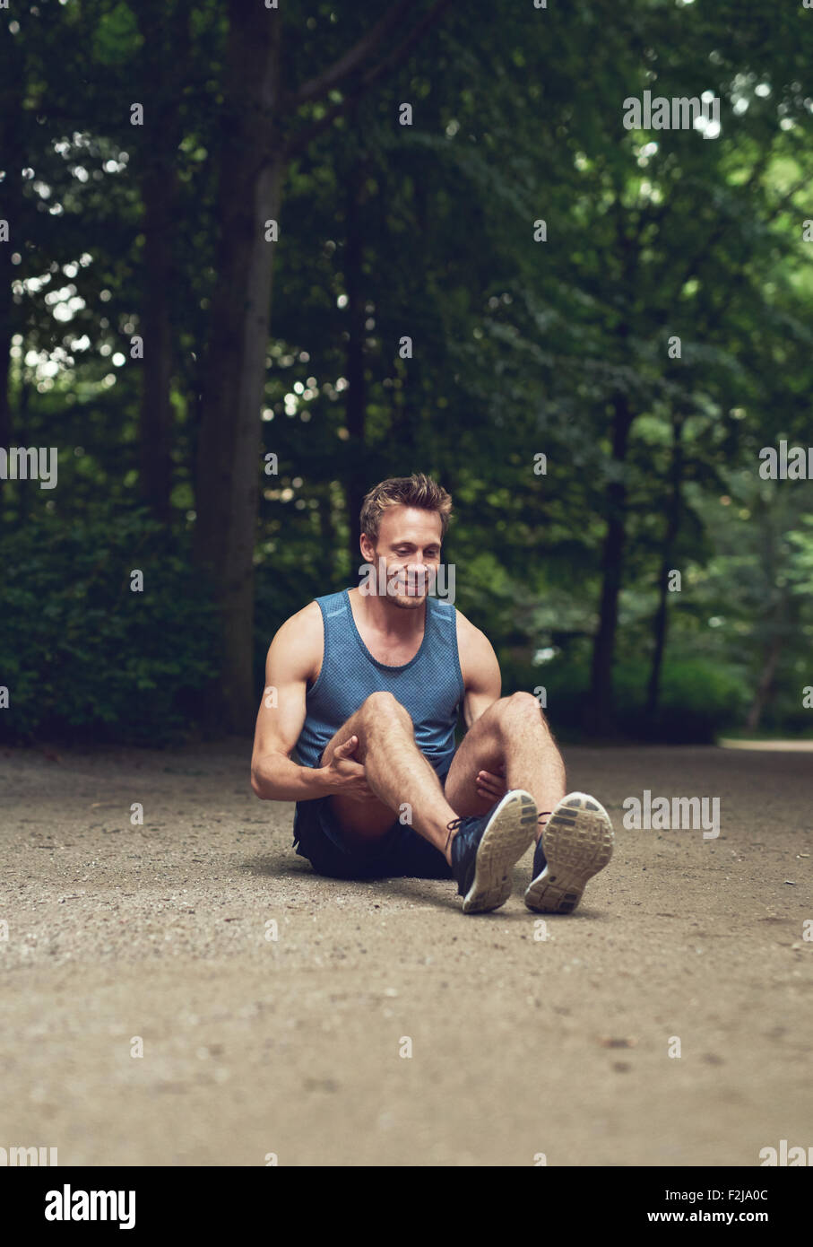 Atletica Giovane Uomo seduto per terra al Parco e flettendo la gamba il warm-up di esercizio, con felici espressioni Immagini Stock