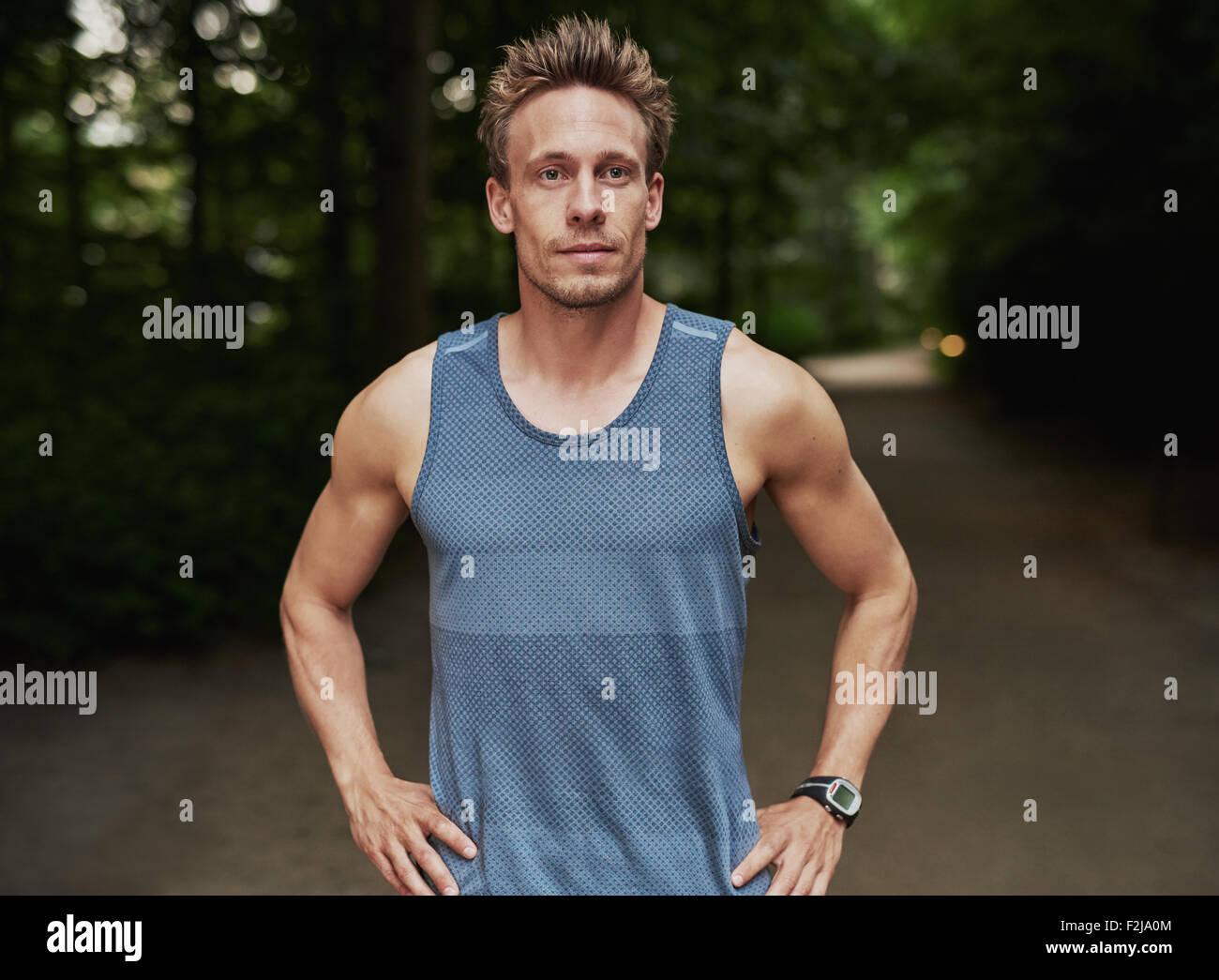 Mezzo Corpo colpo di una Preparazione Atletica Giovane uomo in piedi al parco con le mani sulla cintura e guardando Immagini Stock