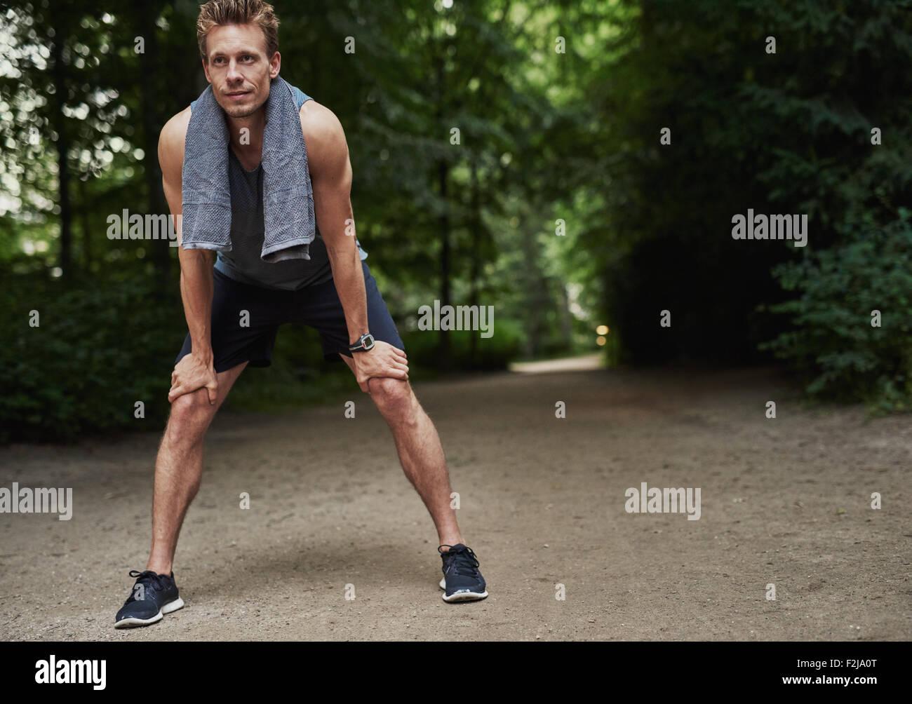 Montare il giovane uomo tenendo le sue ginocchia durante il riposo dopo un esercizio in esecuzione presso il parco. Immagini Stock