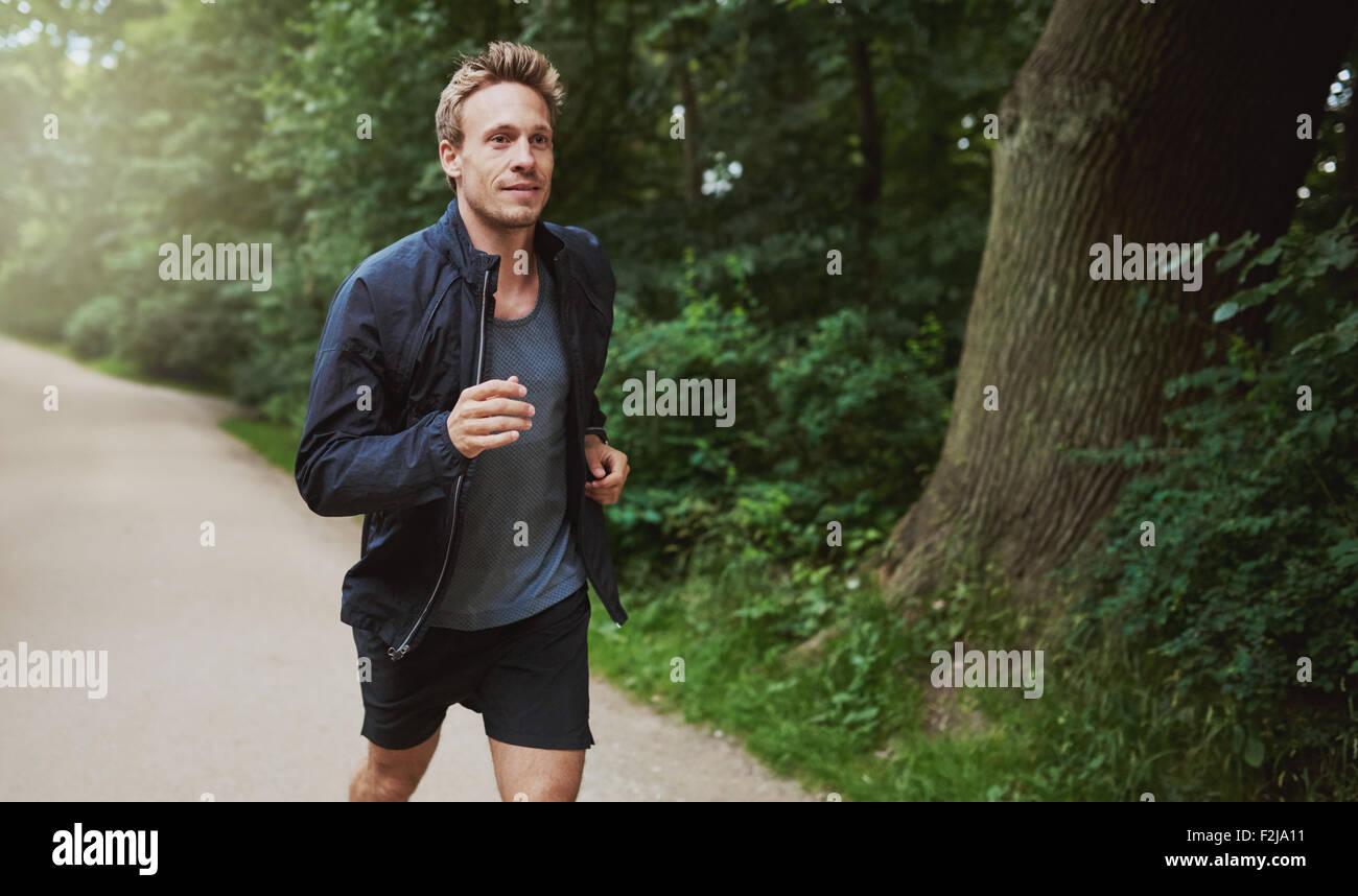 Tre quarti di colpo di un sano Giovane Uomo in camicia Shirt, Jogging al parco di mattina presto. Immagini Stock