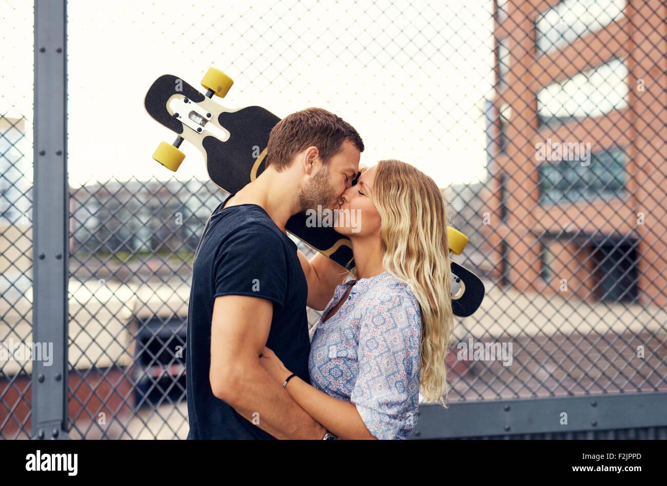 Coppia adorabile kissing permanente, mentre in un parco della città Immagini Stock