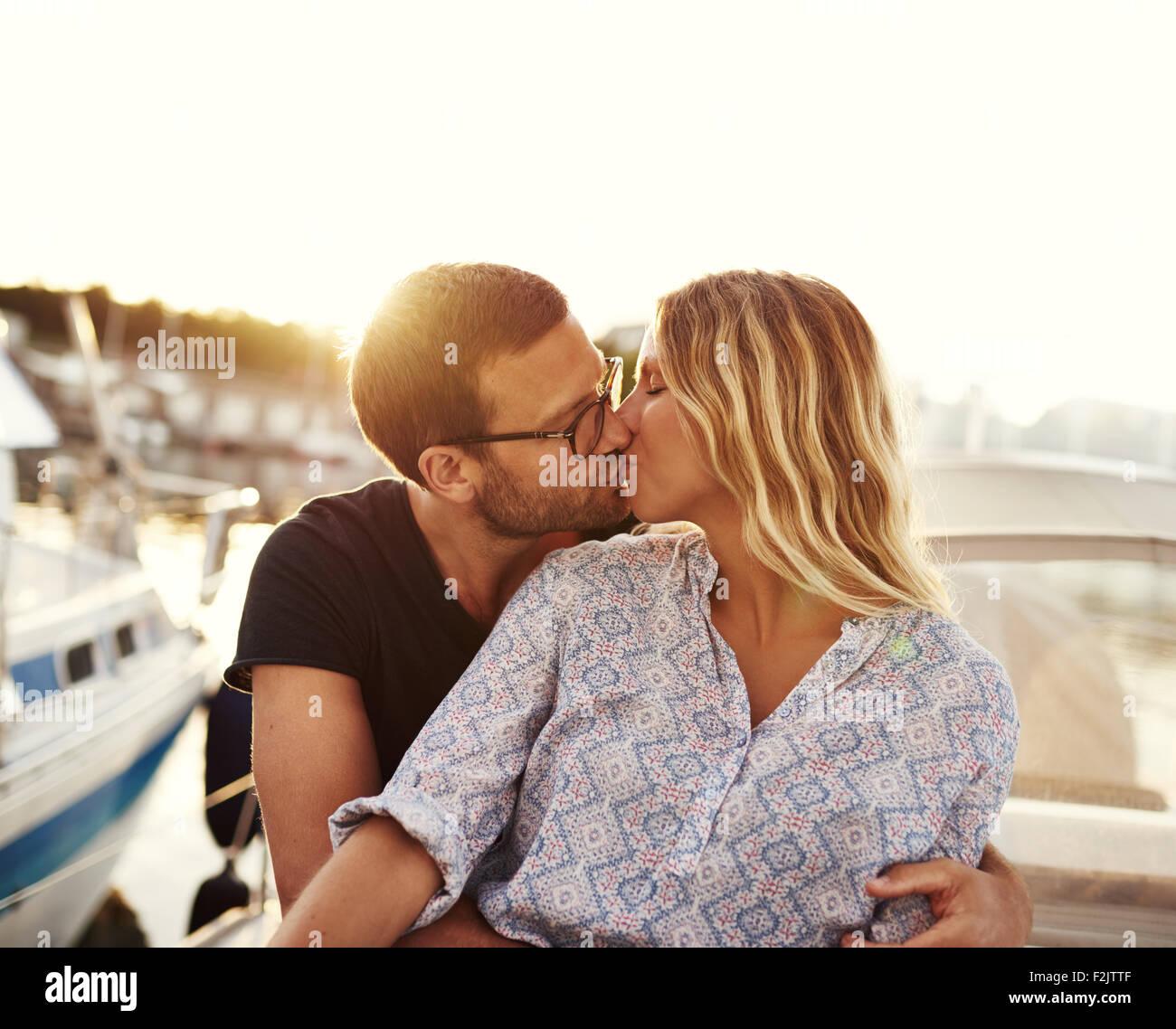 L uomo e la donna baciare su una barca, impostazione di Sun Immagini Stock