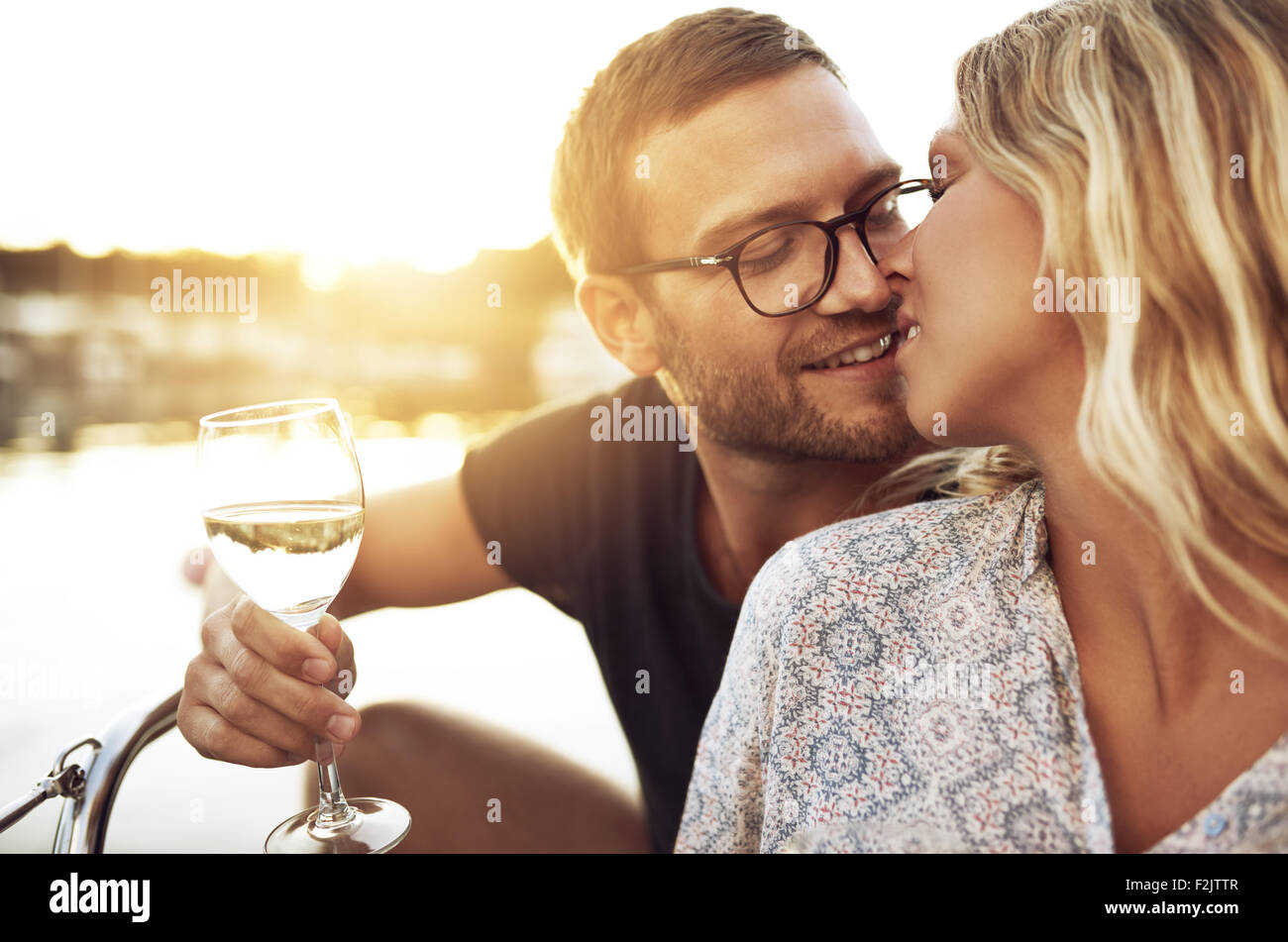 Giovane bacia dolcemente mentre sorseggiate un bicchiere di vino Immagini Stock