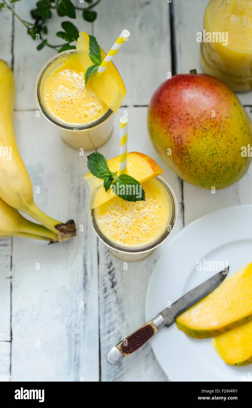 Due bicchieri di mango frullato di banana Immagini Stock