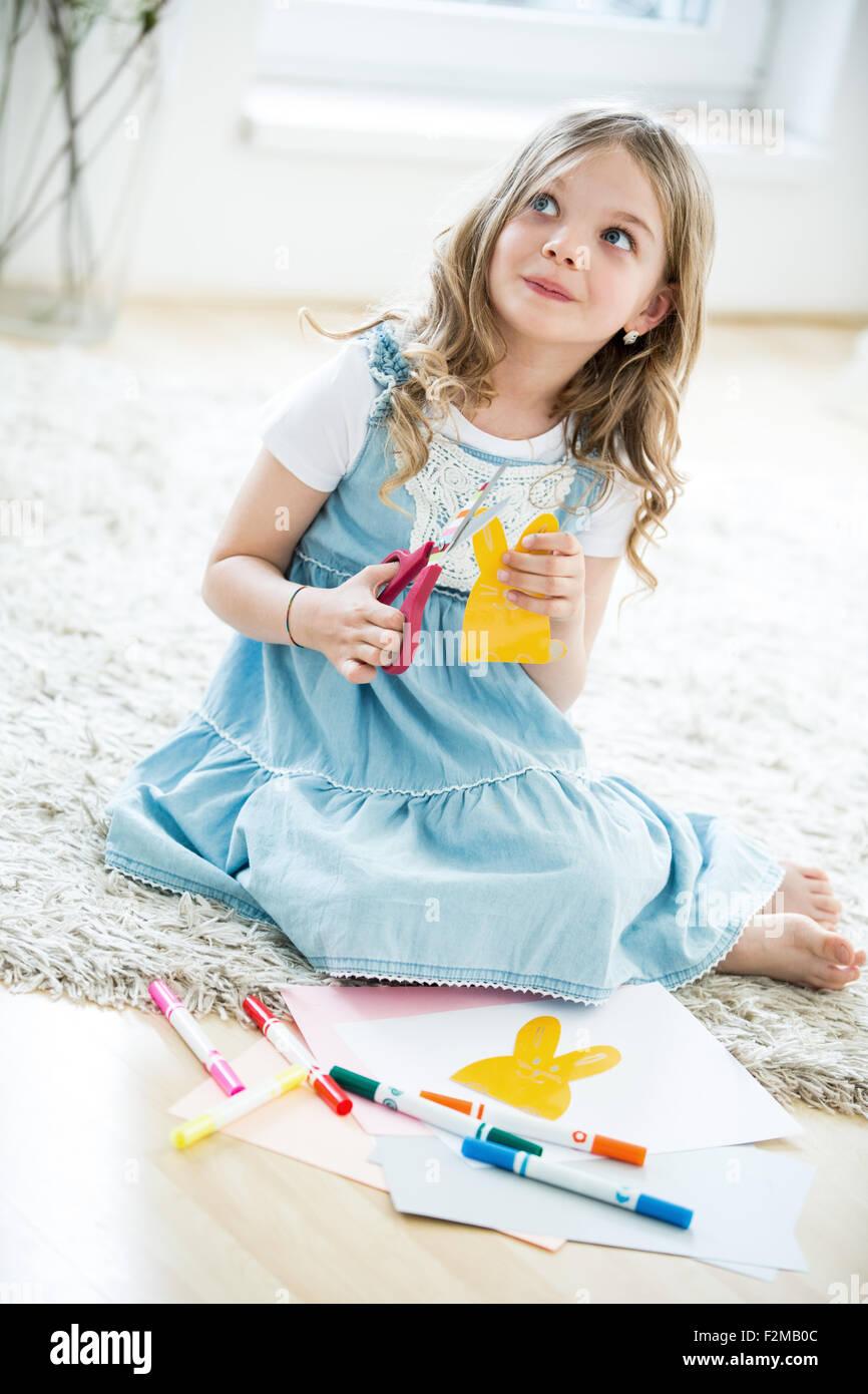 Bambina taglio carta conigli pasquali Immagini Stock