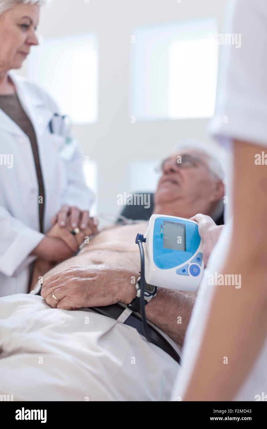 Senior uomo facendo chek fino in ospedale, guardando preoccupato Immagini Stock