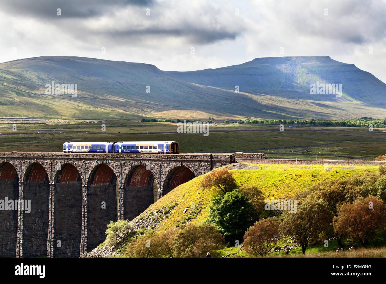 Nord del convoglio ferroviario che attraversa il viadotto Ribblehead con Ingleborough al di là di Yorkshire Immagini Stock