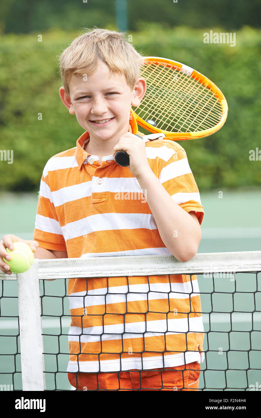 Ritratto di ragazzo giocando a tennis in piedi accanto a Net Immagini Stock