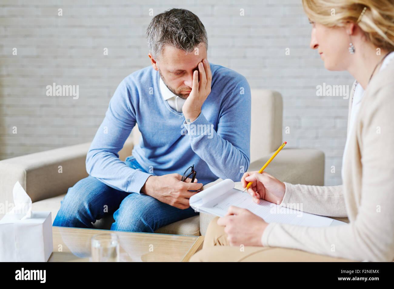 Paziente infelice visitando il suo psicologo Immagini Stock
