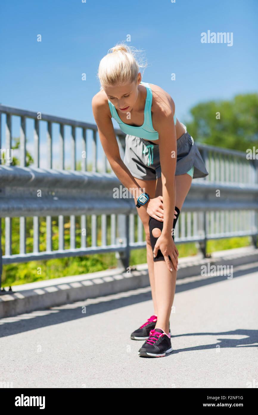 Giovane donna con il ginocchio infortunato o la gamba all'aperto Immagini Stock