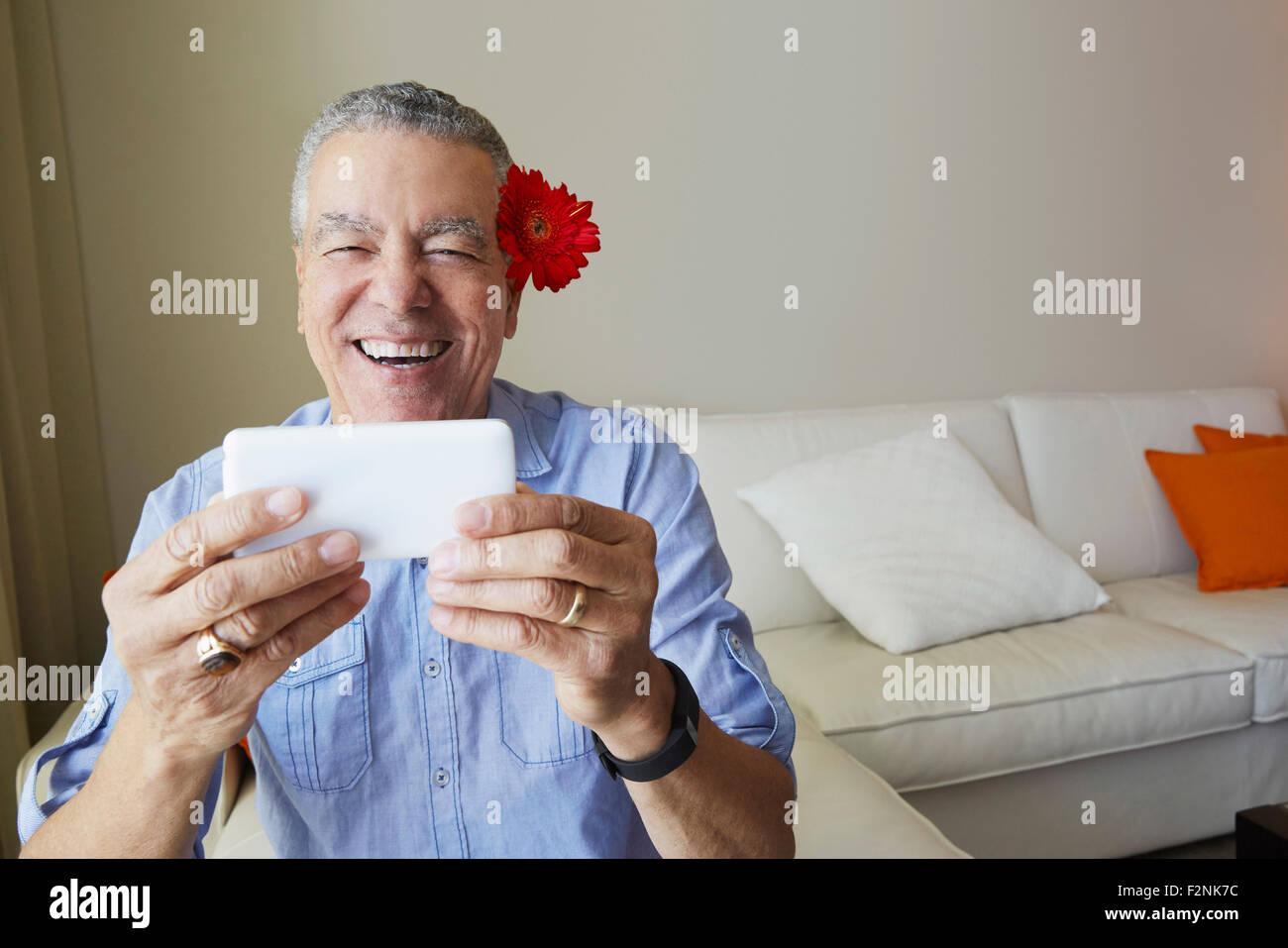 Vecchio Uomo nero tenendo selfie con fiore dietro il suo orecchio Foto Stock