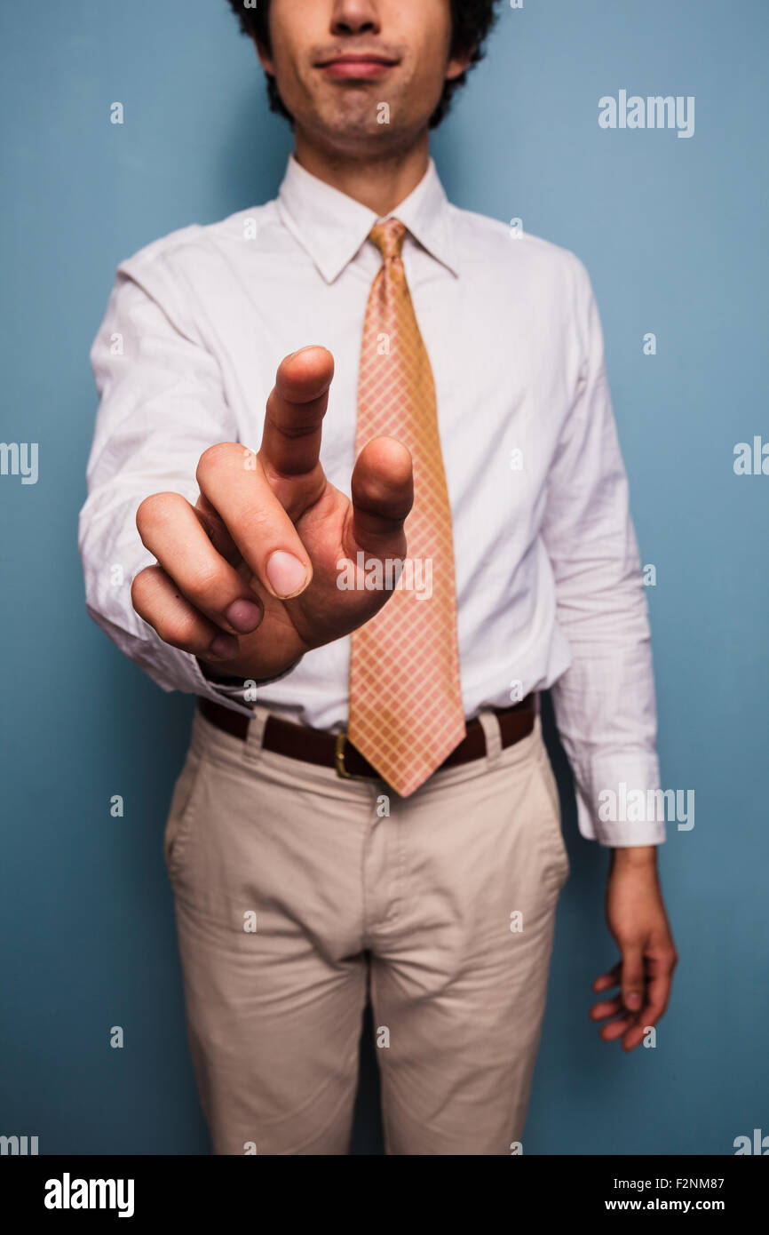 Giovane uomo in piedi da una parete blu e spingendo il pulsante immaginario Foto Stock