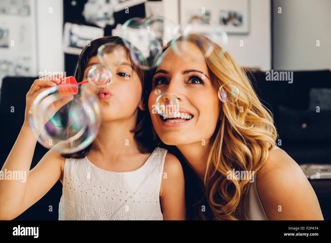 Felice madre con la figlia a casa soffiando bolle di sapone Immagini Stock